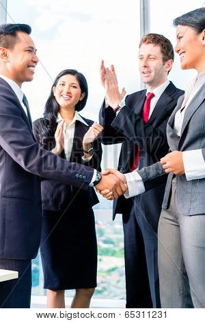 Businesspeople shaking hands in office