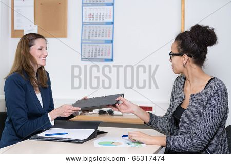 Business Woman Is Handing Over A File To Another Woman