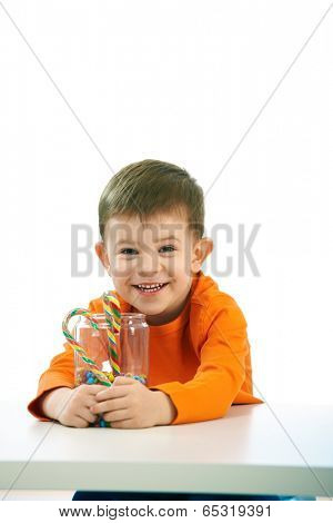 Happy child ( four years old little boy ) eating sweets, isolated on white background.