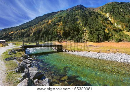 Starting famous Krimml waterfalls. Crystal clear water sparkles in the midday sun. Through the narrow creek wooden bridge spanned. Austrian Alps