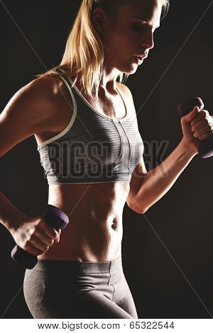 Body of slim female in activewear during exercise with dumbbells