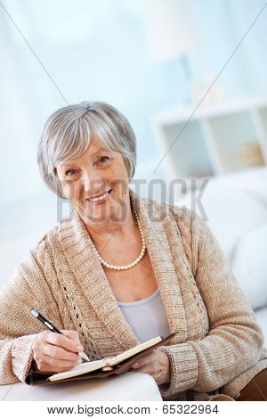Portrait of aged female looking at camera while making notes in notebook