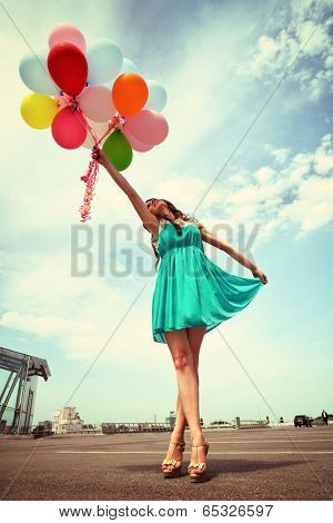Happy romantic fashion girl with colorful balloons, outdoors. Toned.