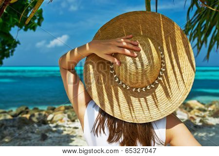 Woman with sun hat at tropical beach
