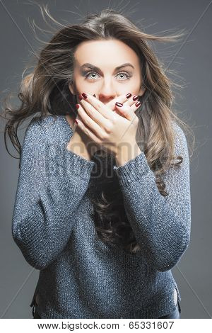Portrait Of Surprised And Silent Female Model Against Gray Background