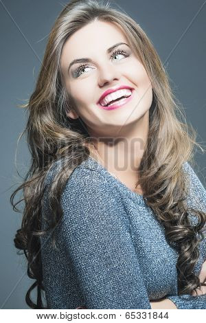 Happy Laughing Beautiful Young Woman  With Natural Brown Long Hair And Vivid Make Up. Against Gray
