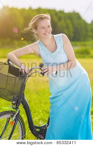 Young Caucasian Blond Laughing Outdoors Standing Near Her Bicycle In The Park