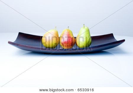Three delicious fresh colorful pears in a wooden vase on the table