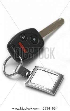 Car key with wireless remote and panic button button showing a blank tag for custom text - Shallow depth of field!