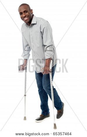 Man Walking With Crutches Isolated On A White