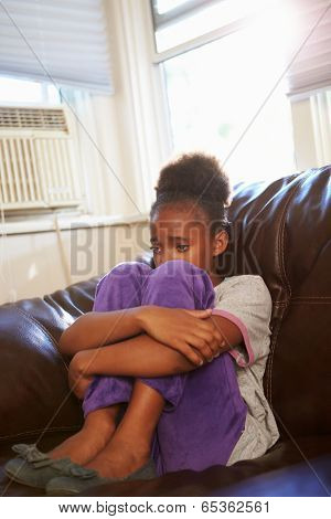Unhappy Girl Sitting On Sofa At Home