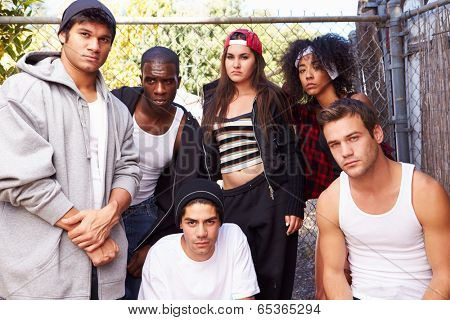 Gang Of Young People In Urban Setting Standing By Fence