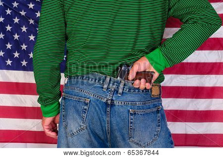 Man with a hand on a  gun in the back of his jeans standing in front of a US flag