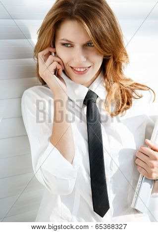 Business woman holding folder in her hand and talking on the phone
