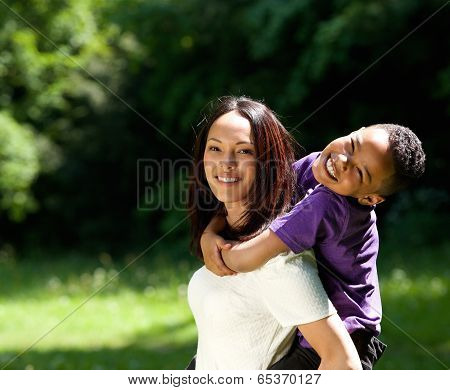 Mother With Son Enjoying Piggyback Ride