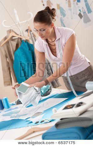 Diseñador de moda femenina trabaja en el estudio