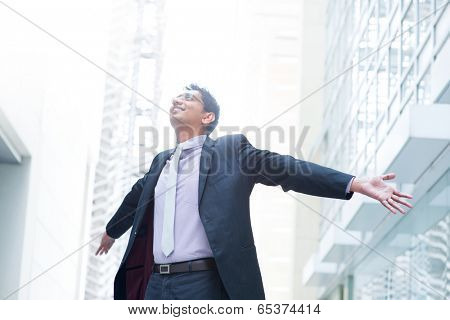 Indian businessman open his arms wide, looking up into the light, modern office building as background, natural sunlight.