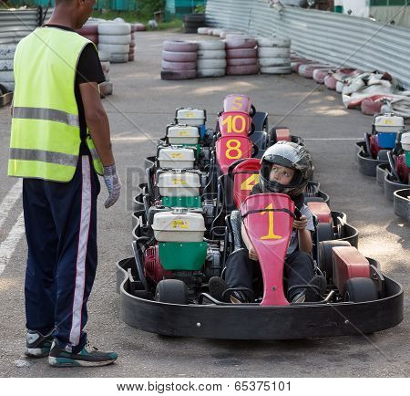 The child prepares for starting on a go-cart in carting club