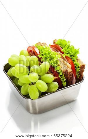 Lunch box with sandwich and grapes on white background