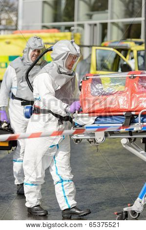 Biohazard medical team with stretcher on street wear protective uniform
