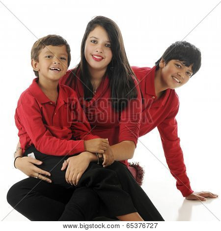 An adorable biracial preschooler sitting on his teen sister's lap.  His tween brother is peeking out from behind them both.  On a white background.