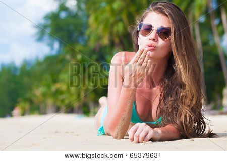 front view of long haired young woman in bikini lying on tropical beach