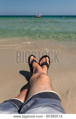 Man's Legs Relaxing At Beach