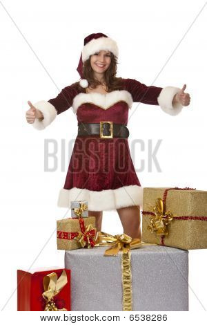 Young Santa Claus Woman Presenting Christmas Gift Boxes With Thumb Up