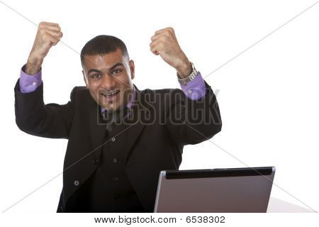 Successful young handsome Businessman at Desk In Office Is Cheering Hurray
