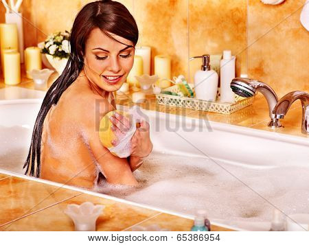 Young woman take bubble bath in bathroom.