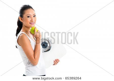 Young Asian woman losing weight by living healthy and eating fruits