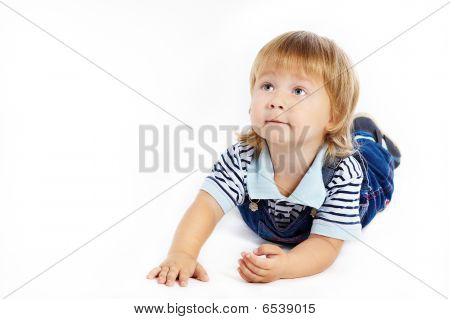 The little boy in dark blue overalls lies on a floor