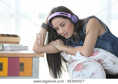 Young Woman Relaxing On An Armchair At Home, Listening To Music With A Stereo And Headphones
