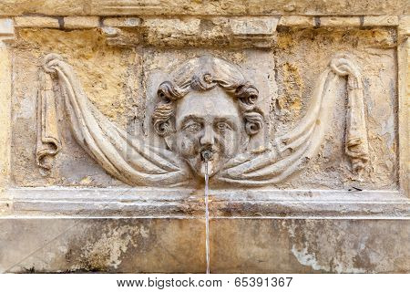 An ancient cherub fountain on the island of Malta.