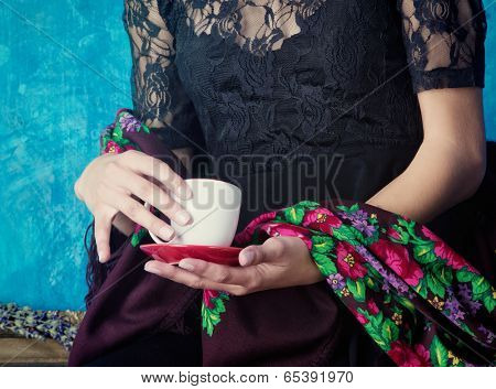 closeup of hands of woman holding a cup of coffee against blue painted grunge wall, wearing black lace and floral shawl