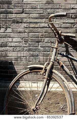 Old Bike Leaning Against Brick Wall In A Chinese Hutong