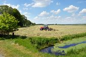 pic of spreader  - A farm tractor pulling a hay rake in a field to clew the grass in a Dutch landscape - JPG