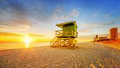 foto of lifeguard  - Miami South Beach sunrise with lifeguard tower and coastline with colorful cloud and blue sky - JPG