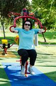 picture of lats  - Mature woman training on a Lat Pull machine at outdoor fitness circuit in the green sunny park