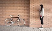 pic of sportive  - Beautiful young sportive woman posing with custom fixie bike over a orange brick wall on the background - JPG