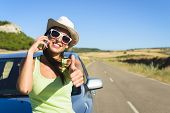 stock photo of gesture  - Successful happy woman on cellphone call enjoying summer car travel vacation and doing approval positive gesture with thumbs up - JPG