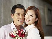 foto of fiance  - portrait of happy young couple smiling with flowers - JPG