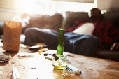 stock photo of bong  - Man Slumped On Sofa With Drug Paraphernalia In Foreground - JPG