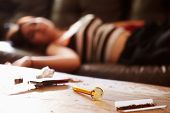 picture of crystal meth  - Woman Slumped On Sofa With Drug Paraphernalia In Foreground - JPG