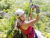 stock photo of canopy  - Woman going on a jungle zip line adventure - JPG