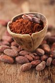 stock photo of cocoa beans  - cocoa powder in spoon on roasted cocoa chocolate beans background - JPG