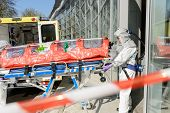picture of stretcher  - Biohazard medical team member with stretcher entering contaminated building - JPG