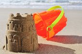 stock photo of bucket  - an orange toy bucket and a sandcastle on the sand of a beach - JPG