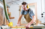 stock photo of sawing  - Carpenter working on an electric buzz saw cutting some boards - JPG