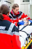 pic of accident victim  - Emergency doctor and nurse or ambulance team transporting accident victim on stretcher - JPG